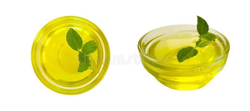 Olijfolie in een glas, geïsoleerd blad stock foto