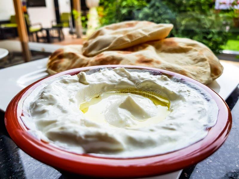Olijfolie in een kom labneh, een heerlijke traditionele Arabische onderdompeling van de yoghurtroomkaas, met vers-gebakken vlak b royalty-vrije stock foto's