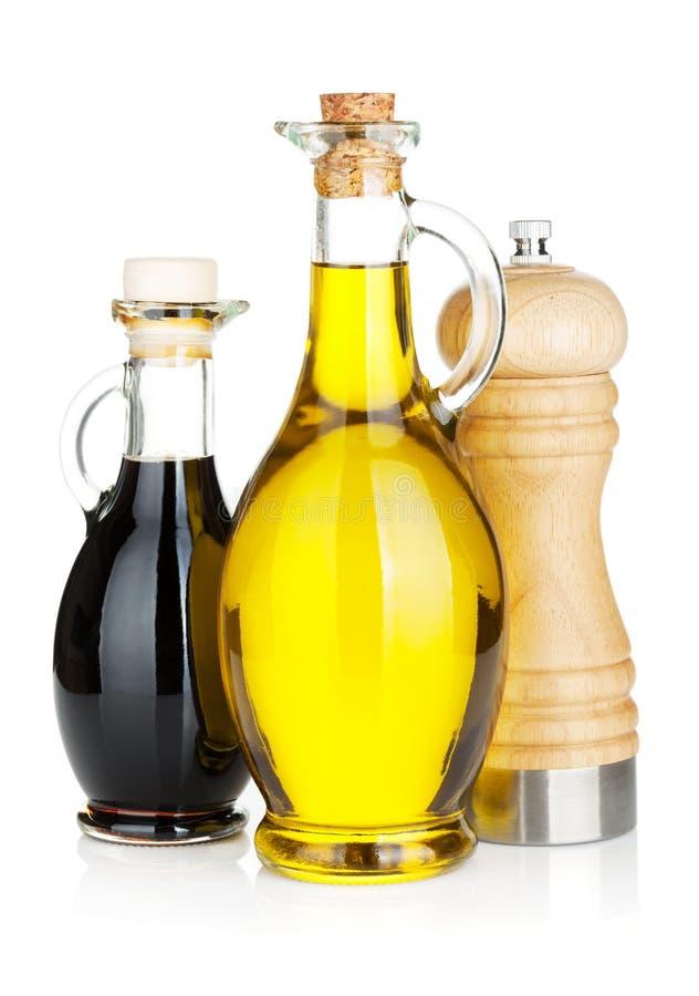 Olijfolie en azijnflessen met peperschudbeker stock fotografie