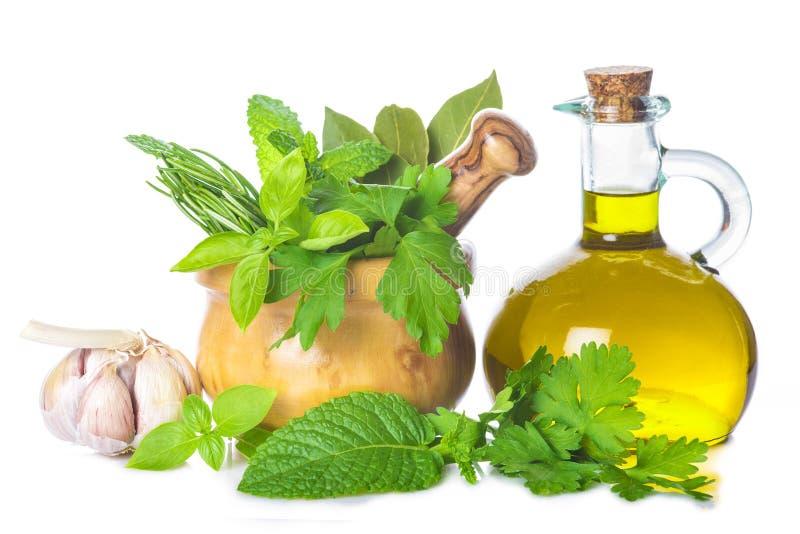 Olijfolie en verse kruiden en kruiden op witte achtergrond stock fotografie