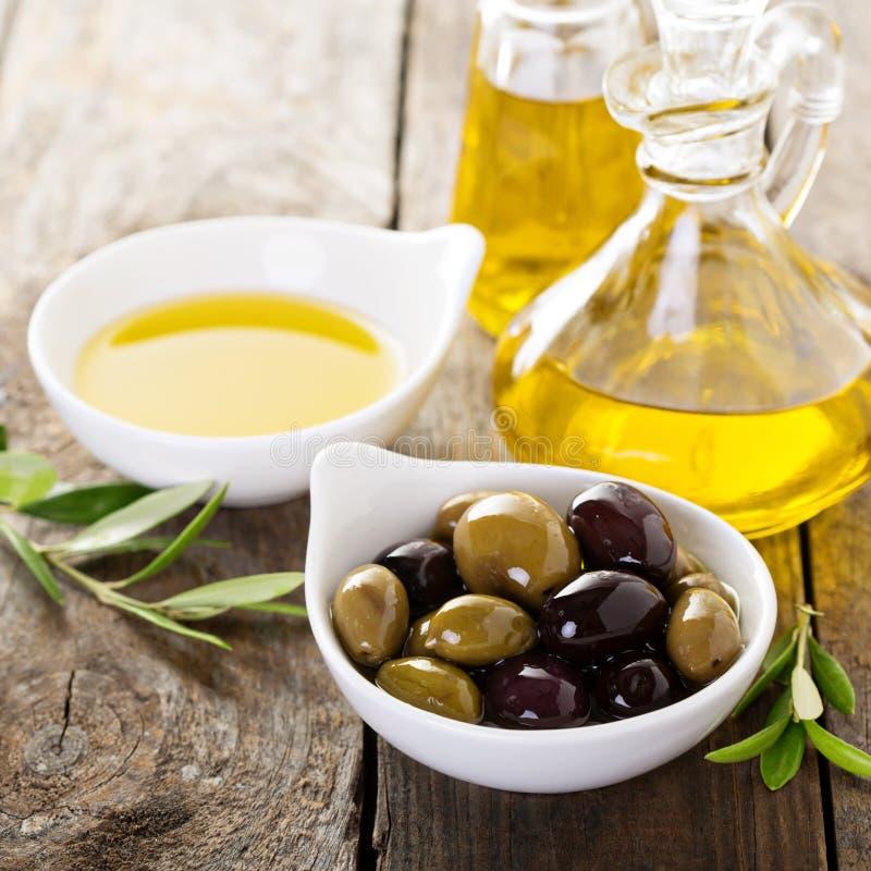 Olijfolie in flessen en een kom met olijven royalty-vrije stock fotografie