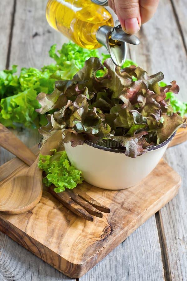 Olijfolie het pourling op groene salade royalty-vrije stock foto's