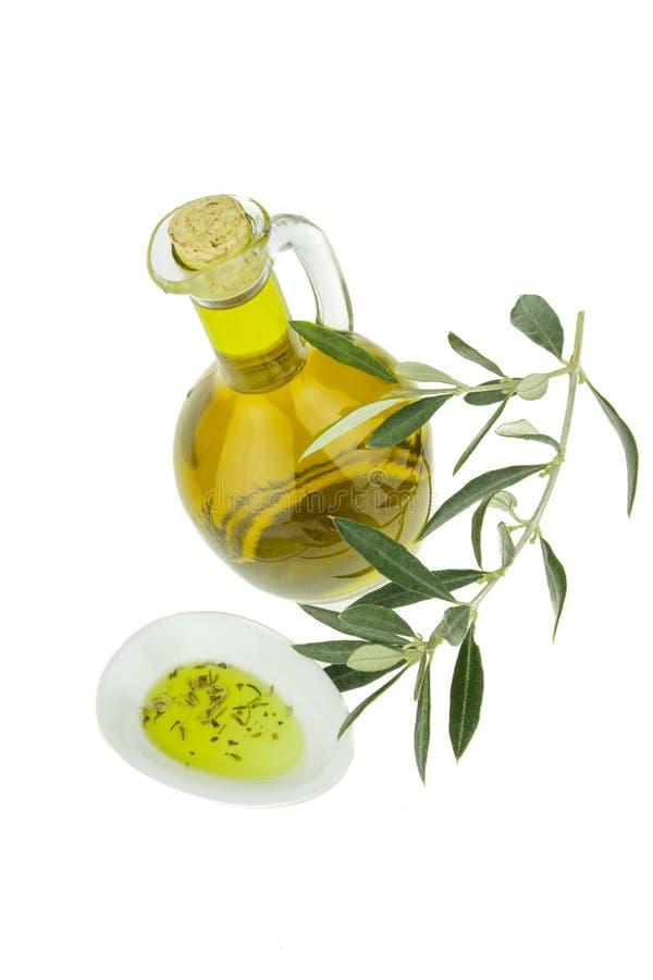 Olijfolie met kruidenfles en komplaat met olijftak Maagdelijke olijfolie Natuurlijke olijfolie, gezond voedsel stock afbeelding