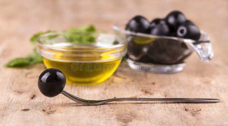 Olijfolie met verse kruiden en olijf op vork op houten backgrou stock afbeeldingen