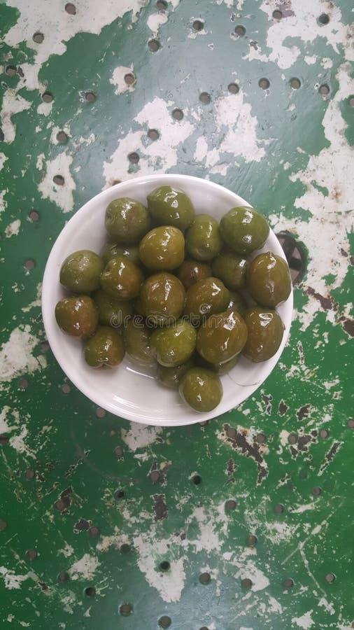 Olijven in een witte kom op een groene lijst stock foto's