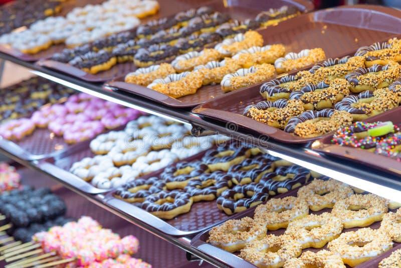 Olik färgrik utsmyckad donutsmunkförsäljning på hylla arkivfoton