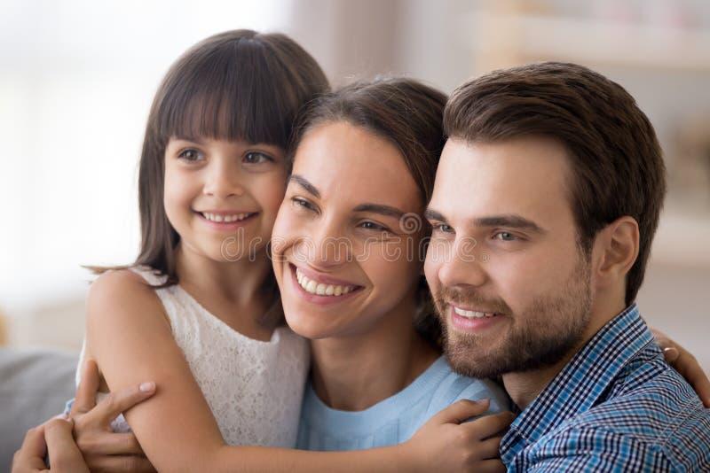 Olik familj med den lilla dottern som ser kameran arkivfoton