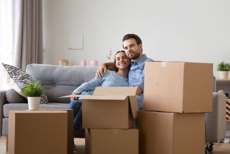 Olik familj som sitter på soffan på det nya hemmet royaltyfri fotografi