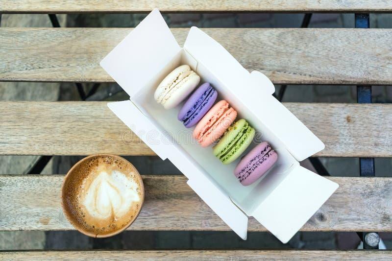 Olik fransk makronkaka i pastellfärgade färger med en kopp kaffe arkivfoton