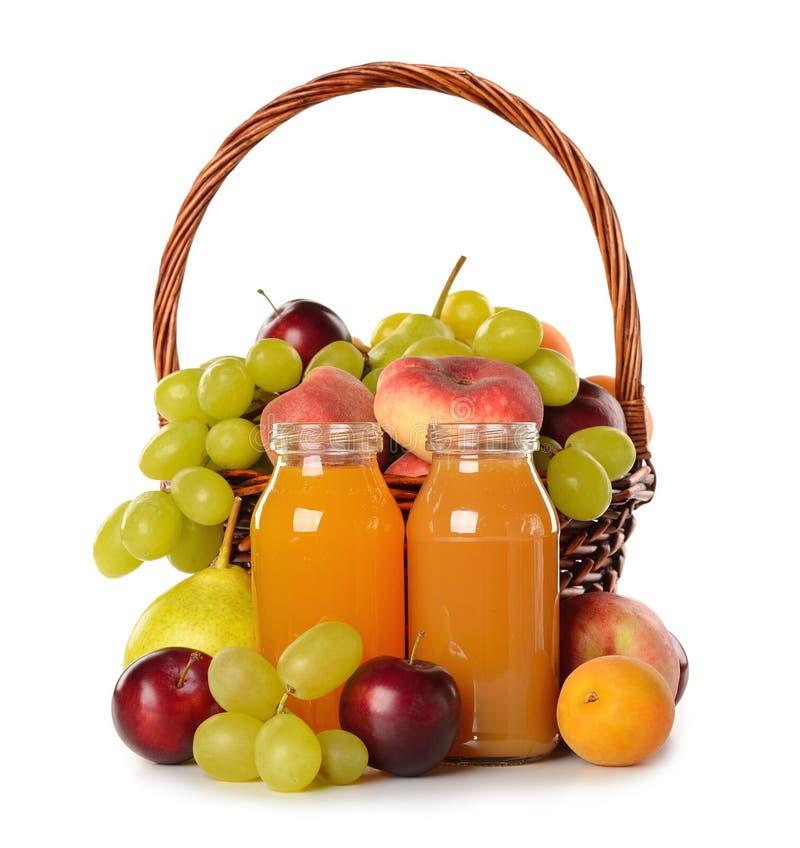 Olik frukt i en korg och en fruktsaft royaltyfri fotografi