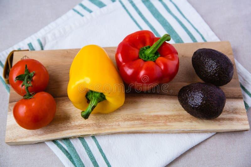 Olik grönsak på träskärbräda arkivfoton