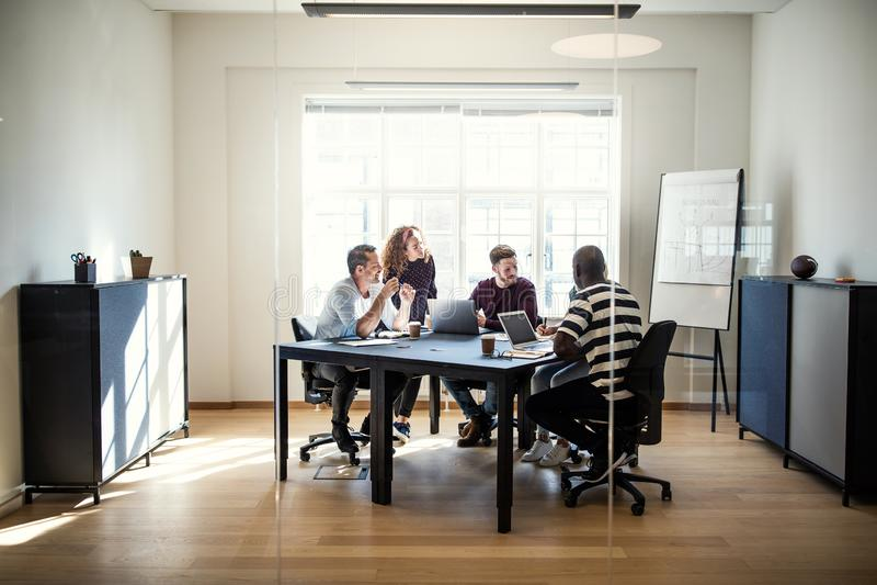 Olik grupp av formgivare som tillsammans möter runt om en kontorsflik arkivbilder