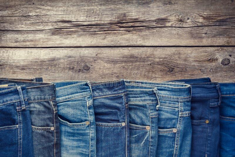 Olik jeans på träbakgrund Tonat Retro royaltyfria bilder