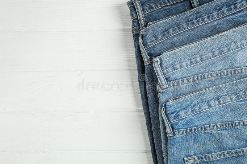 Olik jeans vek på en vit träbakgrund fotografering för bildbyråer
