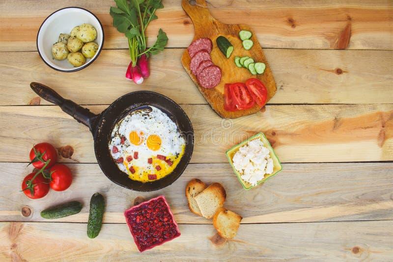 Olik mat: förvanskade ägg i stekpanna, kokta potatisar, ostmassa, driftstopp från viburnumen, krutonger, rädisor, gurkor, tomater royaltyfria foton