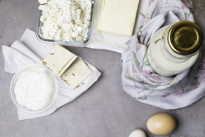 olik mejeriprodukt på grå färgtabellen med blommahandduken arkivbild