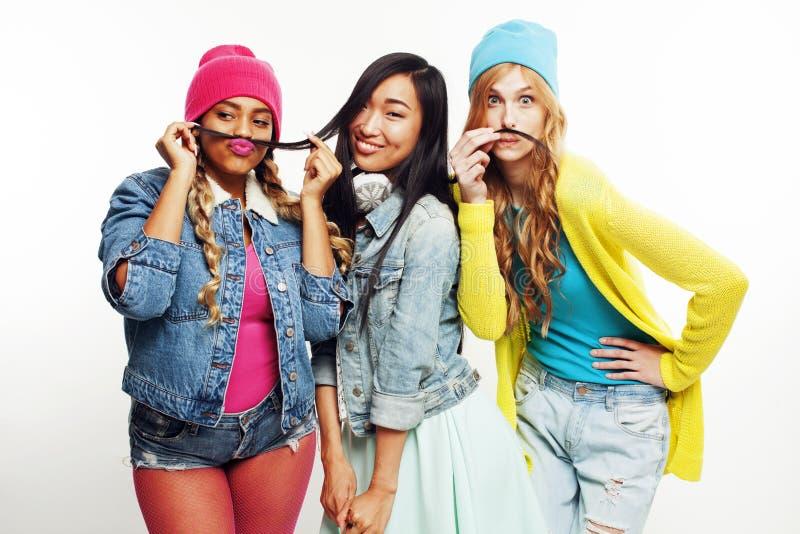 Olik nationflickagrupp, tonårs- gladlynt vänföretag ha gyckel, lyckligt le, gulligt posera som isoleras på vit arkivfoton