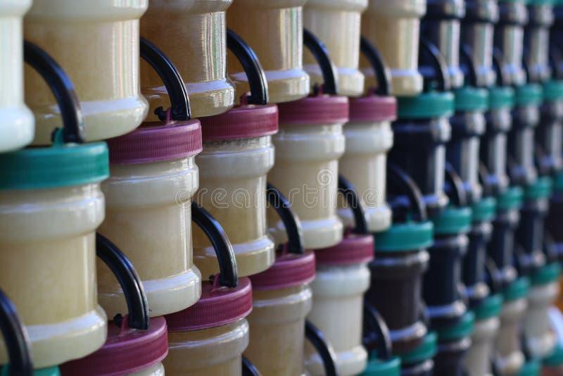 Olik naturlig smaklig honung i plast- krus royaltyfri foto