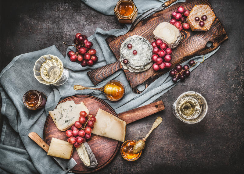 Olik ost tjänade som på lantliga skärbrädor med druvan och vin, mörk tappningbakgrund arkivbilder