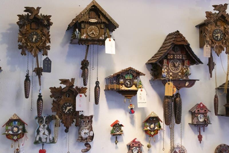 Olik schweizisk gökur på en vägg för att sälja arkivbilder