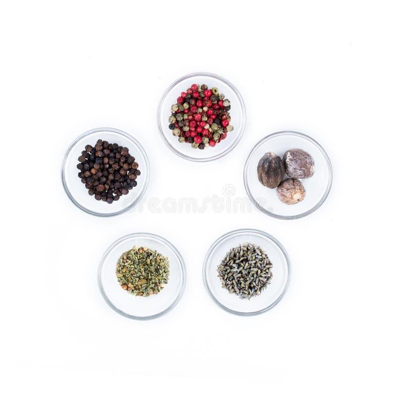 Olik sort fem av torra kryddor på exponeringsglaskoppar från över royaltyfria bilder