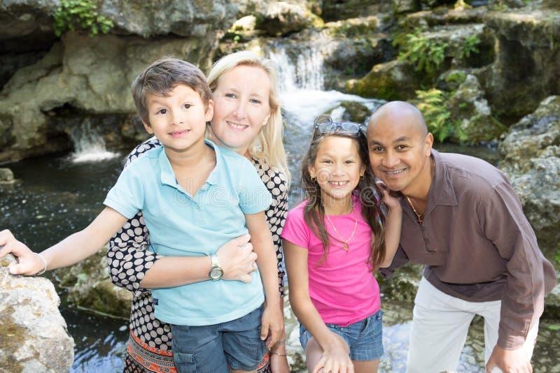olik stående av en lycklig familj som besöker i parkera arkivfoto