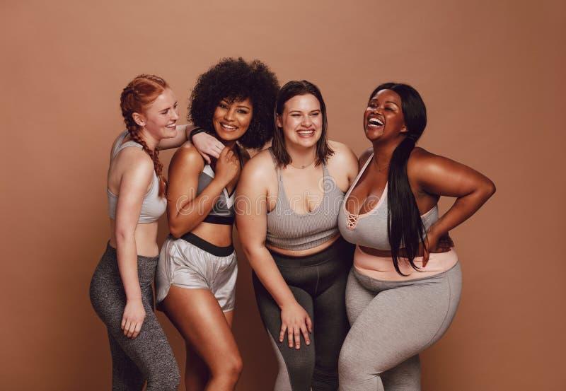 Olik storleksanpassad kvinna som tillsammans skrattar royaltyfri fotografi