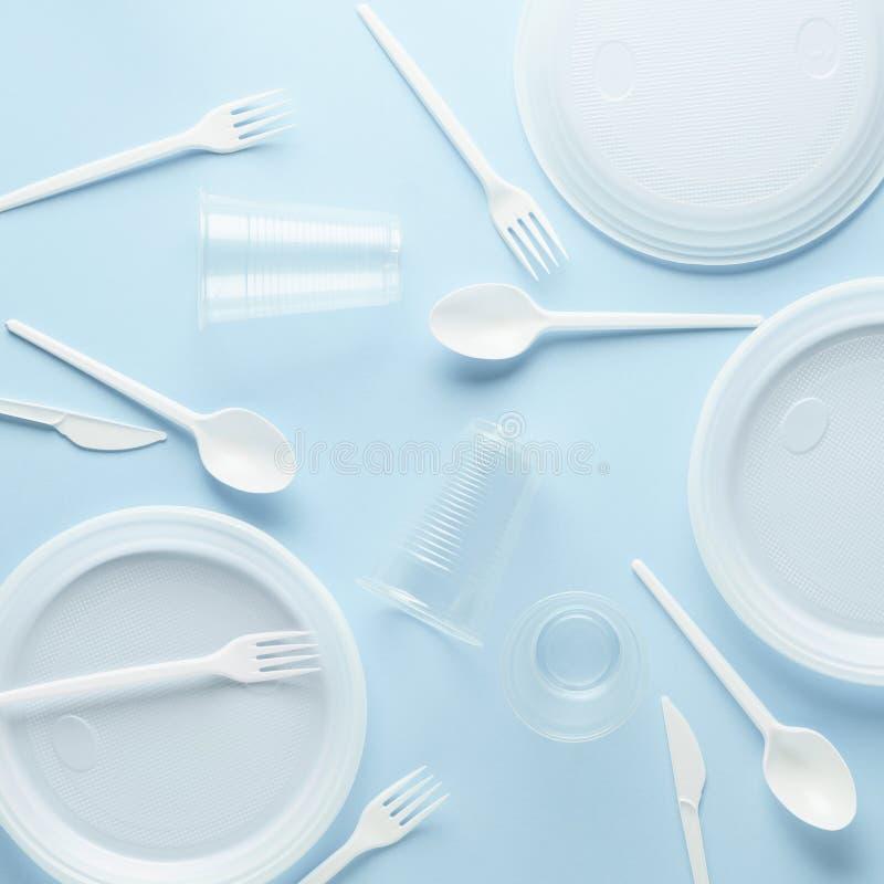 Olik vit plast- disponibel bordsservis på blå bakgrund royaltyfria bilder