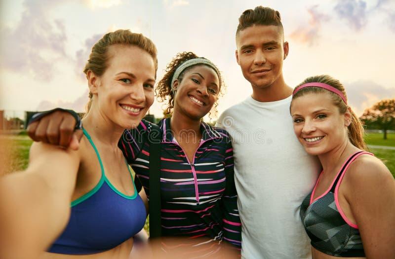 Olik yogagrupp av gladlynta millennial vänner tar en selfie på solnedgången i natur parkerar arkivbilder