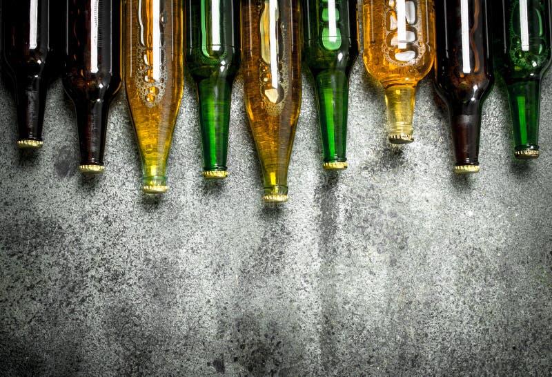 olika ölflaskar På lantlig bakgrund arkivbild