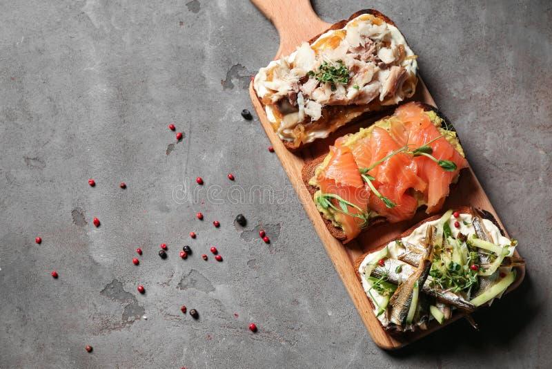 Olika öppna smörgåsar med fisken på den gråa tabellen fotografering för bildbyråer