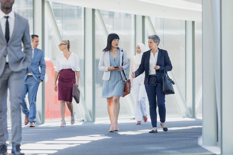 Olika affärskvinnor som påverkar varandra med de, medan gå i korridor fotografering för bildbyråer