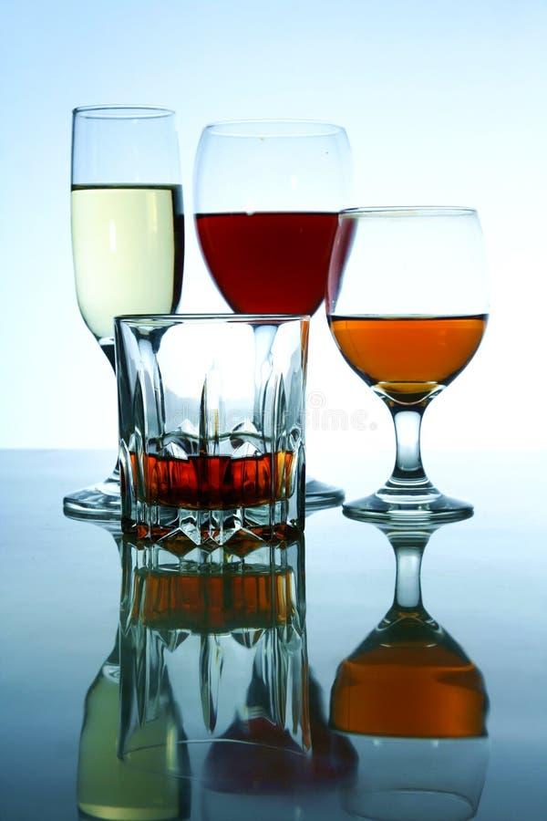 Olika alkoholdrycker i exponeringsglas och bägare arkivbilder