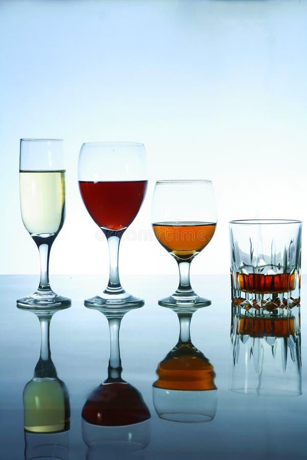 Olika alkoholdrycker i exponeringsglas och bägare royaltyfri fotografi