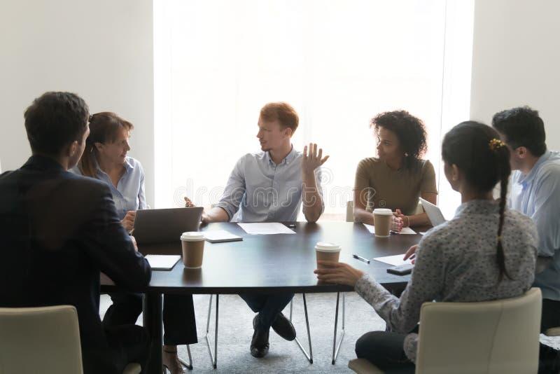 Olika anställda förhandlar idékläckning i konferensrum arkivfoton