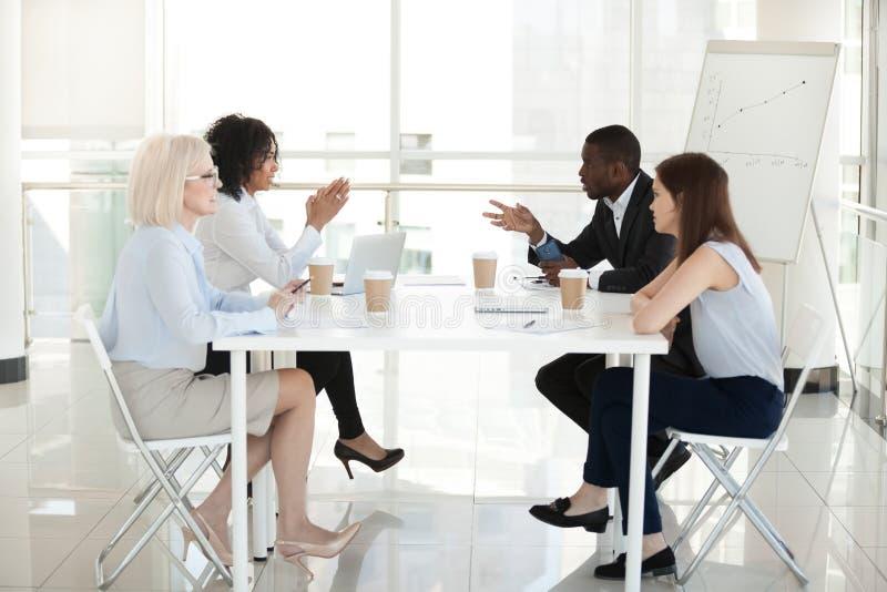 Olika anställda sitter på tabellen som diskuterar projekt i styrelse fotografering för bildbyråer