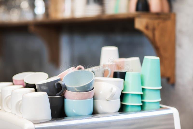 Olika blåa, rosa, vita och gröna koppar i kafé arkivbilder