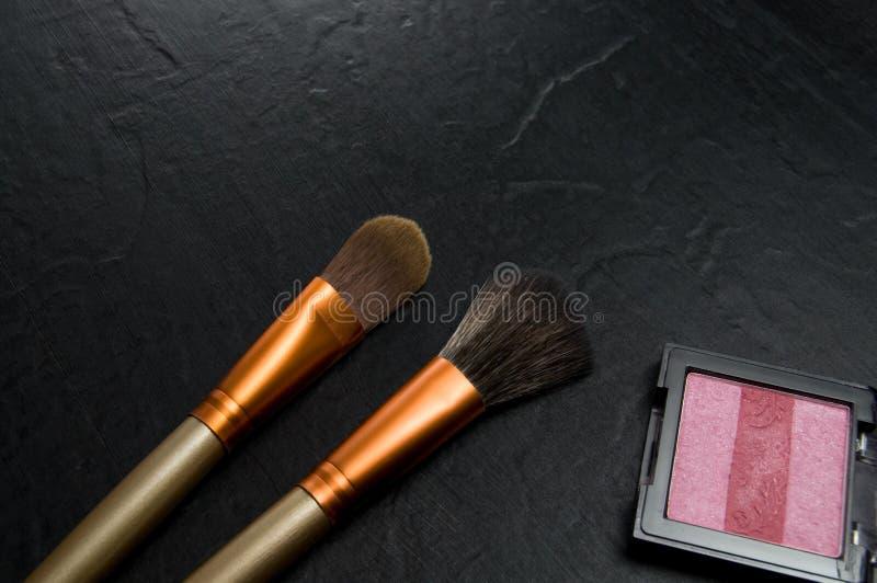 Olika borstar och rosa smink för kvinnor på mörk bakgrund royaltyfri bild