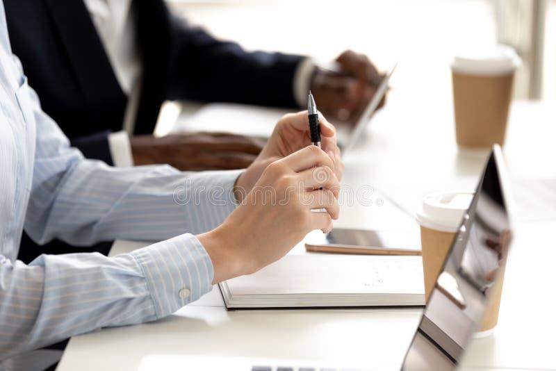 Olika businesspeople för Closeup som sitter på konferenstabellen som lyssnar till högtalaren arkivfoton