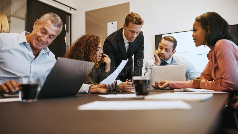 Olika businesspeople som tillsammans diskuterar skrivbordsarbete runt om en nolla royaltyfria bilder