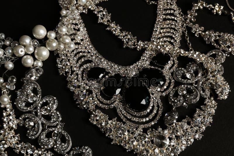 Olika eleganta smycken på svart bakgrund arkivfoton
