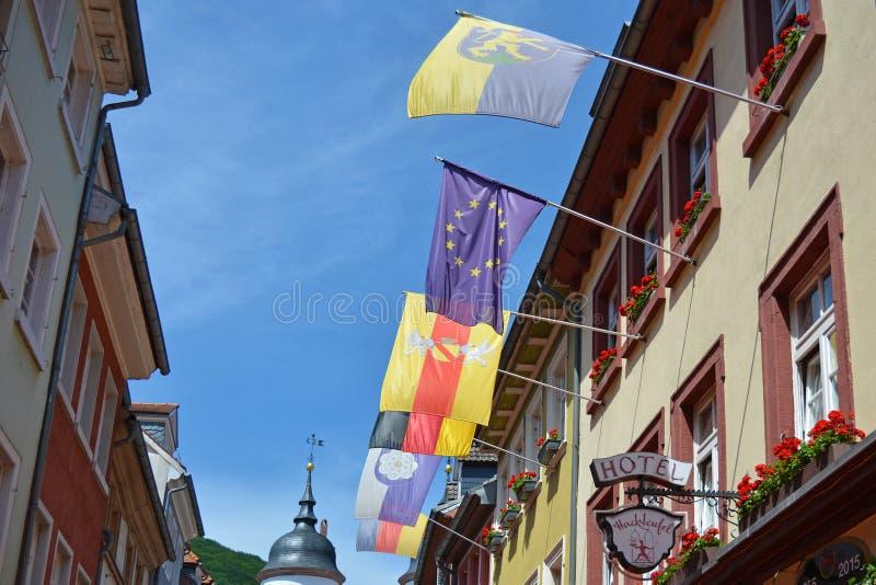 Olika europeiska fackmedlemflaggor som hänger från flaggapoler från gammal historisk byggnad i turist- gata i Heidelberg agains fotografering för bildbyråer