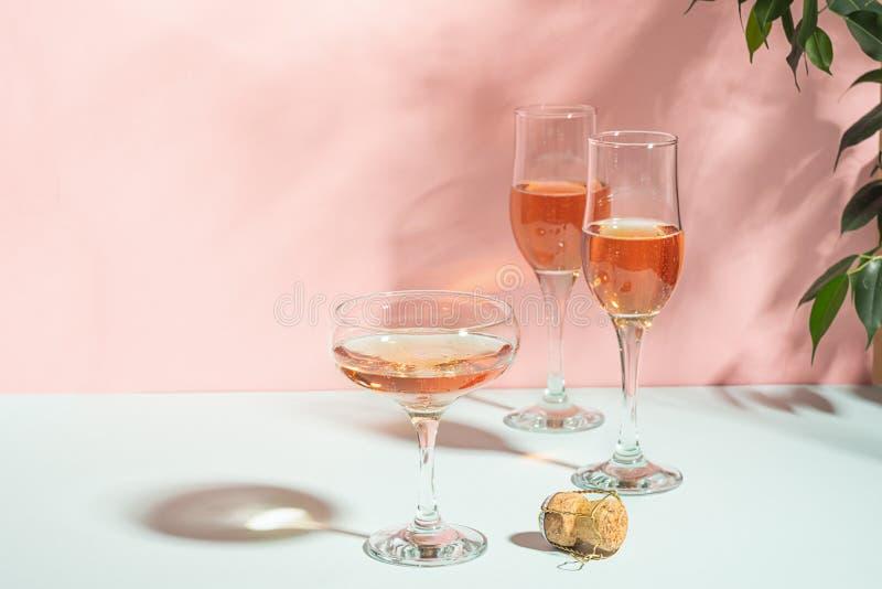 Olika exponeringsglas av champagne eller vin på ett ljust ljus för delikat rosa bakgrund Festligt begrepp kopiera avst?nd royaltyfri bild