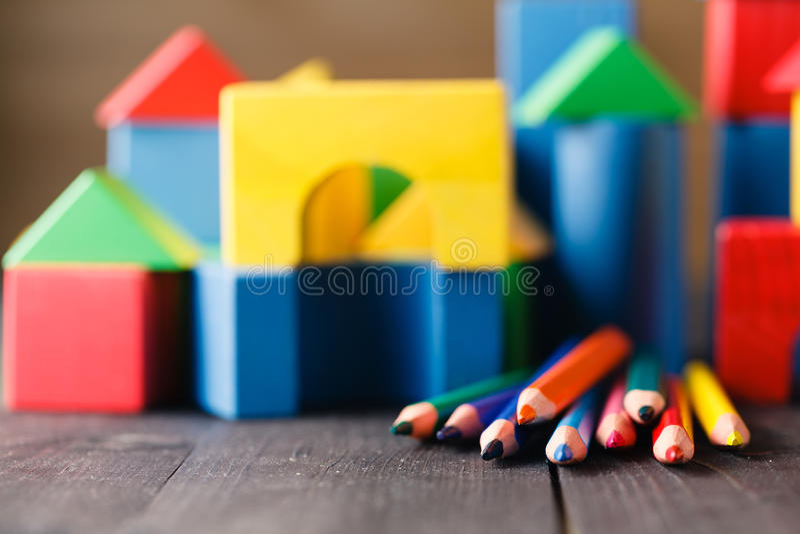 Olika färger av blyertspennor som är ontable med byggnadskvarter fotografering för bildbyråer