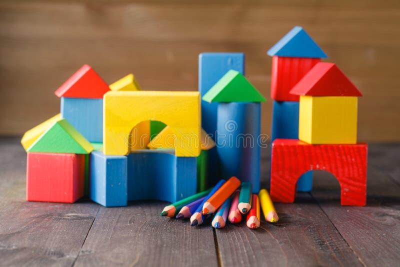 Olika färger av blyertspennor som är ontable med byggnadskvarter arkivbild