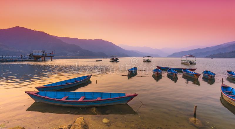 Olika färgfartyg som parkeras i Phewa sjön efter solnedgång arkivfoto
