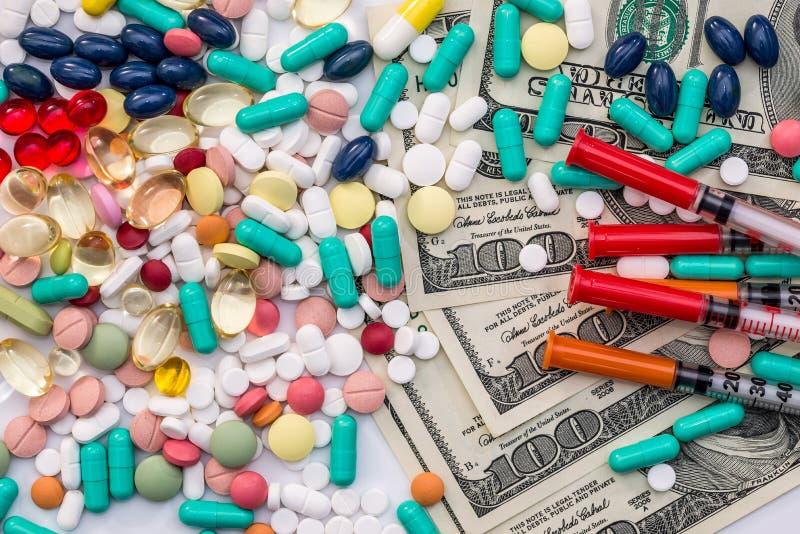 Olika färgpiller med injektionssprutor och dollarsedlar royaltyfri fotografi