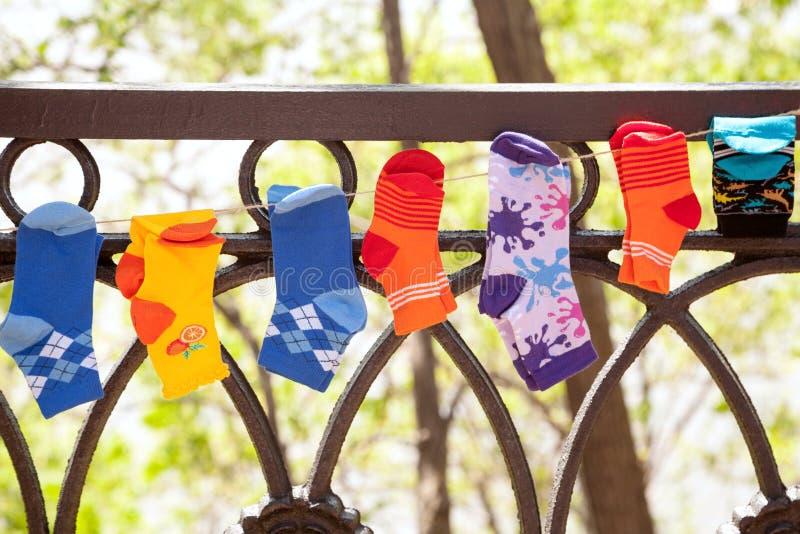 Olika färgrika barnsockor som hänger på en tvagning, fodrar utomhus royaltyfri foto