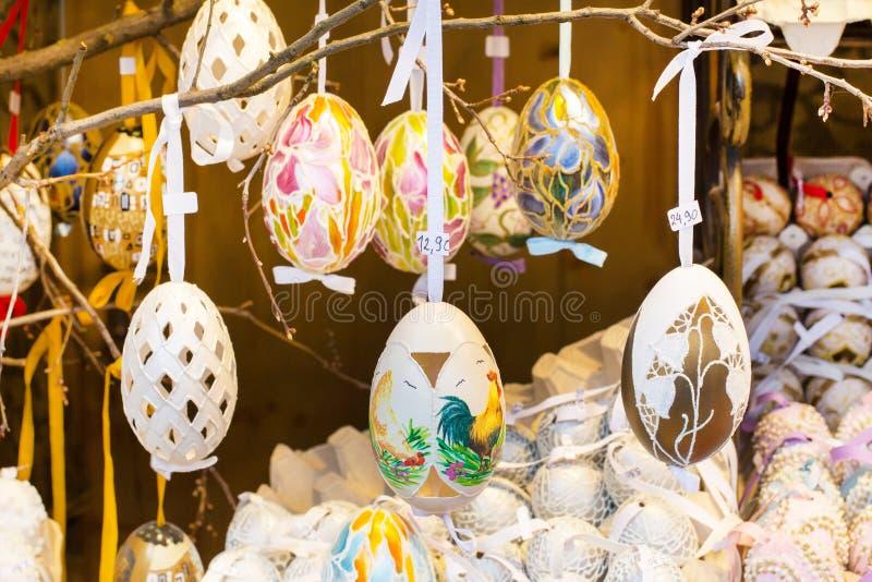 Olika färgrika målade påskägg på trädet på den traditionella europeiska marknaden arkivbilder