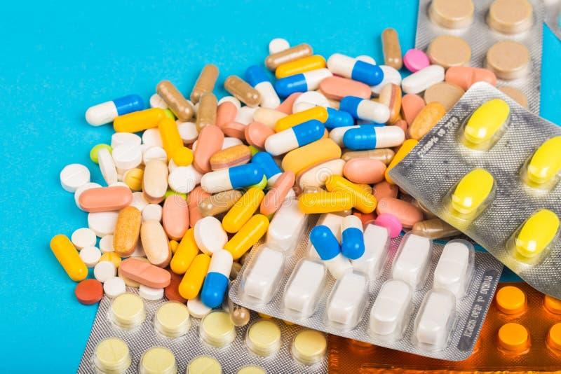 Olika färgrika piller och plast- packar - blåsor som staplas på blå abackground royaltyfri bild